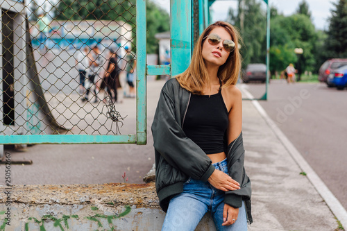 Fashion portrait of trendy young woman wearing sunglasses, jeans with halls and Canvas Print