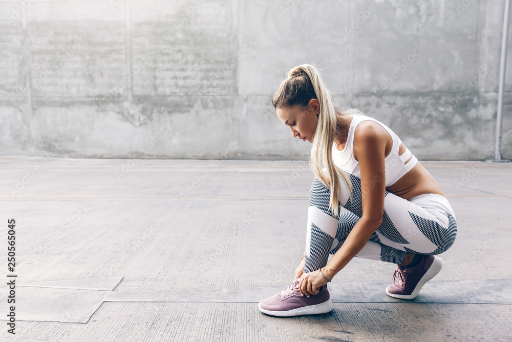Fototapety, obrazy: Fitness sport woman in fashion sportswear doing workout over gray wall