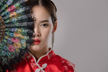Portrait Of Asian At Traditional Chinese Dress. Close Up Fashion Shot Of Asian Woman Holding Chinese Fan Look At Camera On Grey Background Free From Copy Space. Chinese New Year Concept