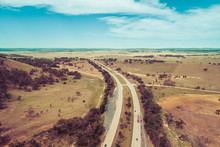 Aerial View Of Cars And Trucks Driving On Hume Highway Among Australian Countryside.