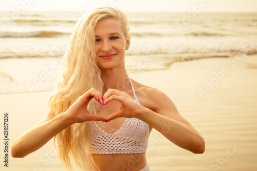 Valokuva  Close up of cheerful young girl in summer hat taking a selfie at the beach and s