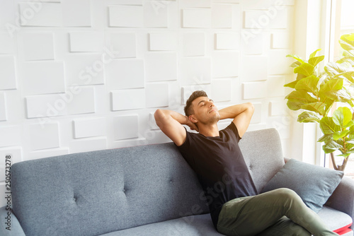 Valokuva  Businessman in casual relaxing on sofa with soft sunlight