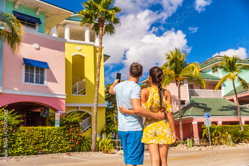 Couple on winter vacation taking pictures of pastel colored beach houses cottages in tropical holiday destination Fort Myers, Florida Canvas-taulu