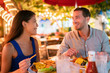 canvas print picture - Couple eating hamburgers at outdoor restaurant terrace happy tourists on summer vacation. Florida travel people eating food at night during holidays in Miami. Asian Caucasian interracial young adults.