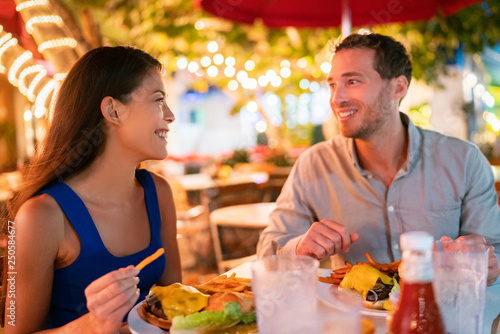 Fotografía  Couple eating hamburgers at outdoor restaurant terrace happy tourists on summer vacation
