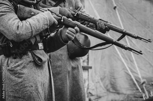 Fototapeta Two German soldiers of the Second World War with rifles in their hands ready to fire