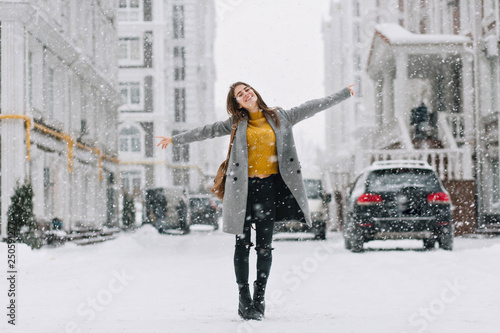fototapeta na szkło Full-length portrait of romantic european lady wears long coat in snowy day. Outdoor photo of inspired brunette woman enjoying free time in winter city.