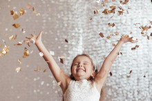 Cute Little Child Girl In Princess Dress On Confetti Background With Silver Bokeh. Birtday Party