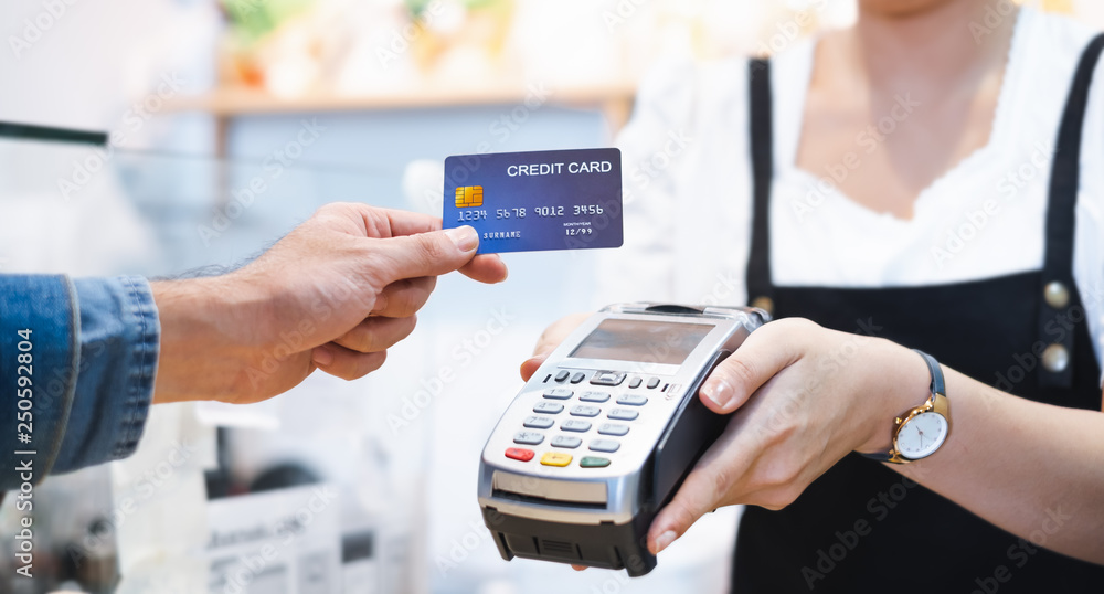Fototapeta Customer using credit card for payment to owner at cafe restaurant, cashless technology and credit card payment concept