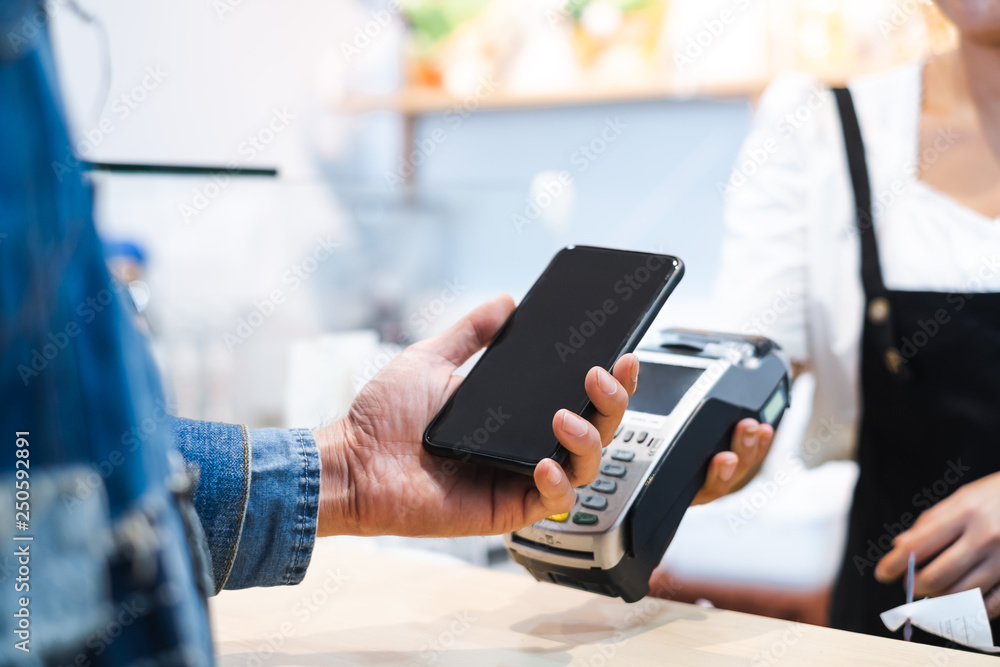 Fototapeta Customer using credit cart for payment to owner at cafe restaurant, cashless technology and credit card payment concept