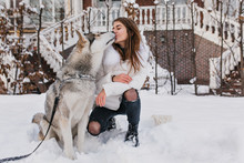 Pretty Caucasian Lady In White Jacket Kissing Her Husky Dog During Walk In Winter Day. Attractive Young Woman Wears Ripped Jeans Playing With Pet In Snowy Morning..