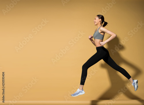 Fotografia  Asian slim Fitness woman exercise warm up stretch spring jumps legs, studio ligh