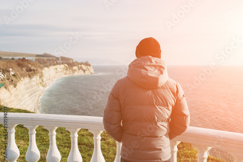 Man looks at sea and rock cliffs at sunset light, be alone with yourself and thoughts
