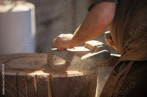 Aluminium Prints Mills Carpenter working with electric planer on wooden stump outdoors