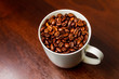 Roasted Coffee beans in a white mug cup isolated on a rustic wood table