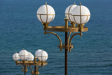 Two Street Lamps With Round Lights On The Background Of The Sea, Concept