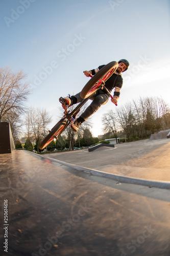 BMX jump in a wooden ramp at skate park.