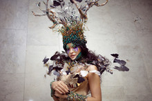 Natural Nymph With Horns Like Branches Of A Tree And Butterflies Circling Around. Fantasy Style Costume
