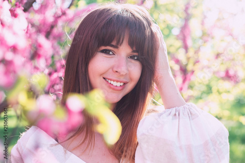 Fotografie, Obraz  Spring fashion portrait of sensual beauty woman, long hairs pastel make up, posing at blossom garden park, sunny hot day, white vintage shirt, straw hat