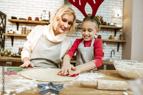 Fotografie, Obraz  Proud entertained mother in striped apron controlling her daughter