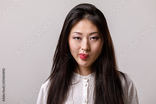Fotografía  portrait of thinking asian woman in glasses and white shirt on gray background