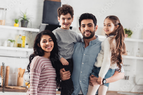 Photo  handsome latin father holding in arms cute daughter and son near attractive wife