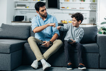 Happy Latin Father Giving Fist Bump To Son After Playing Video Game At Home