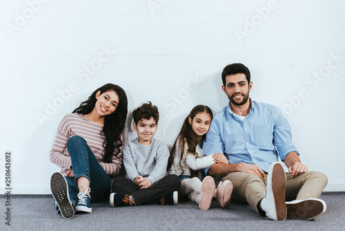 cheerful hispanic family smiling while sitting on floor near white wall Wallpaper Mural