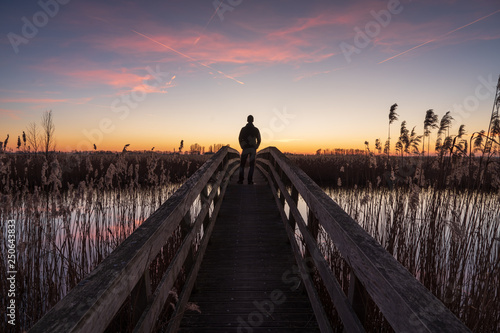 Photo  Man on a small bridge enjoying a tranquil dusk in Holland.