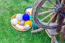Elements Of Old Life. Spinning Wheel And Thread On Green Grass