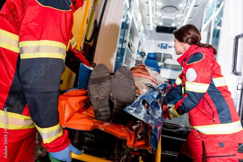 Paramedics transportating patient on gurney in ambulance car Wallpaper Mural