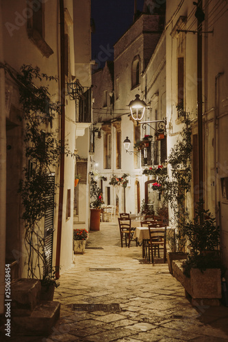 Narrow white street and restaurant tables in Locorotondo, region Puglia, Italy