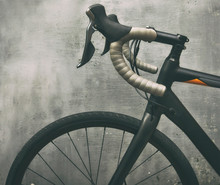 A Black Race Bike In Front Of Metal Gray Wall