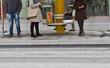 Personen warten bei einer Haltestelle auf ein öffentliche Verkehrsmittel