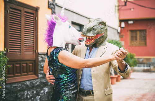 Photo Crazy couple dancing and wearing dinosaur t-rex and unicorn mask - Senior elegan