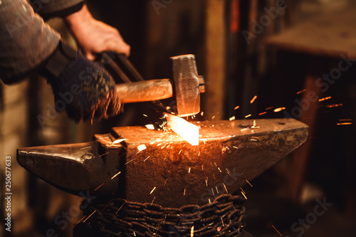 Photo The blacksmith manually forging the red-hot metal on the anvil in smithy with spark fireworks