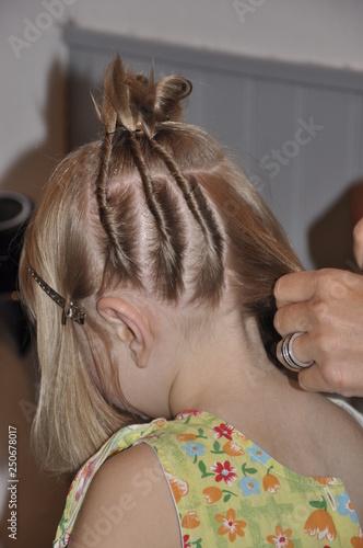 une enfant se fait faire une coiffure Fototapete