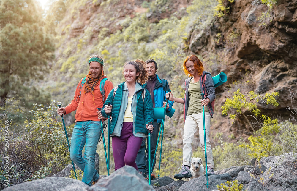 Fototapety, obrazy: Group of friends with backpacks doing trekking excursion on mountain - Young  tourists walking and exploring the wild nature - Trekker, sport, hike and travel concept