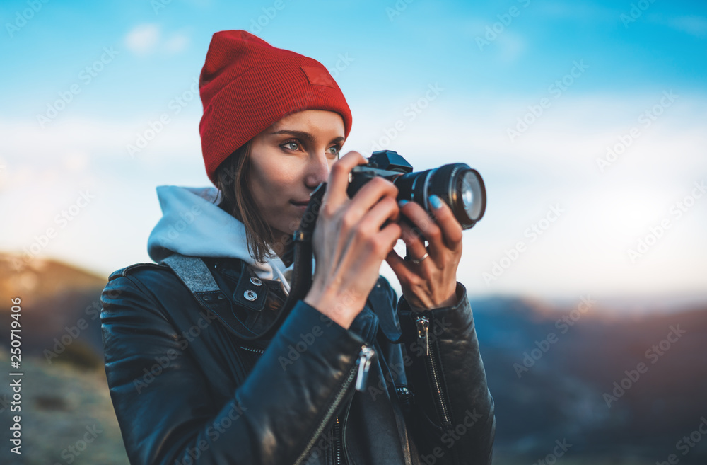 Fototapeta hipster tourist girl hold in hands take photography click on modern photo camera, photographer look on camera technology, journey landscape vacation concept, sun flare mountain - obraz na płótnie