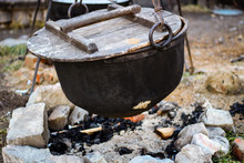 Traditional Cooking Chef In A Cast Iron Cauldron. Food On An Open Flame. Cooking Pan For Many People.