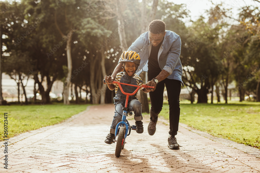 Fototapeta Father teaching his son cycling at park