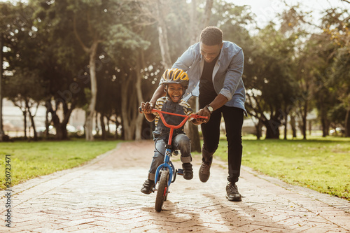 Father teaching his son cycling at park Fototapet