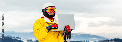 Fotomural Female skier on the top of ski slope using laptop