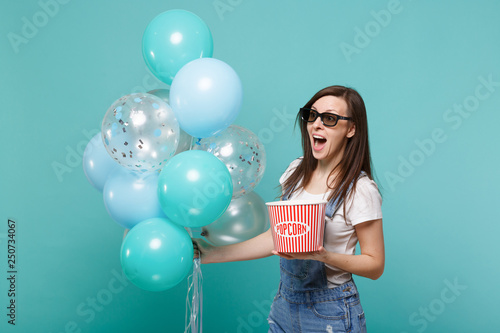 Photo  Excited woman in 3d glasses watching movie film hold bucket of popcorn celebrating with colorful air balloons isolated on blue turquoise background