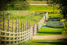 Perspective View Of Long Wooden Fence In The Green Farm. Wooden Fence And Shadow In The Middle Of The Green Grass Field.