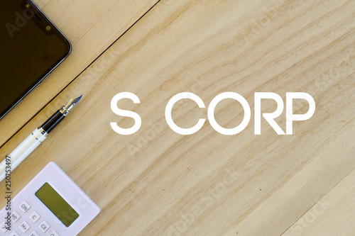 Photo  Top view of mobile phone,pen and calculator on wooden background written with S Corp