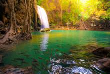 Waterfalls And Fish Swim In The Emerald Blue Water In Erawan National Park. Erawan Waterfall Is A Beautiful Natural Rock Waterfall In Kanchanaburi, Thailand.