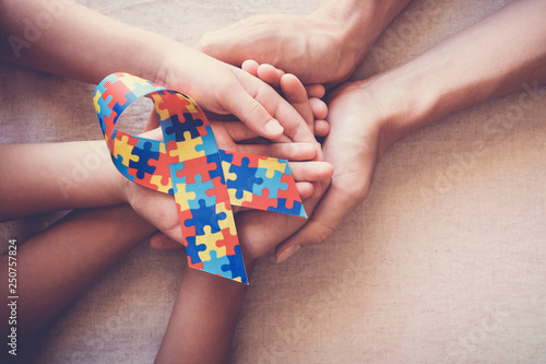 Plakaty Autyzm hands-holding-puzzle-ribbon-for-autism-awareness