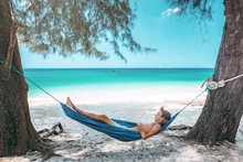 Teenage Boy Chilling In Hammock On The Beach