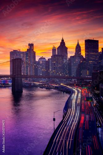 Poster New York TAXI Must see when visiting New York City. View of Lower Manhattan and Brooklyn at sunset. Night scene. Light trails. City lights. Urban living, travel, real estate and transportation concept